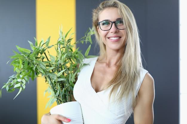 Portrait de jeune femme joyeuse et heureuse tenant un gros pot avec plante