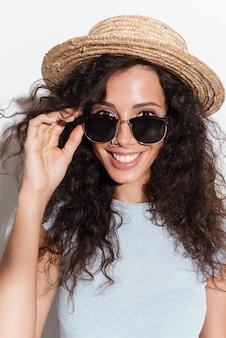 Portrait de jeune femme joyeuse à lunettes de soleil