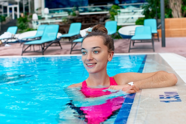 Portrait de jeune femme joyeuse mignonne heureuse nager dans une piscine tout en vous relaxant dans une station thermale de bien-être