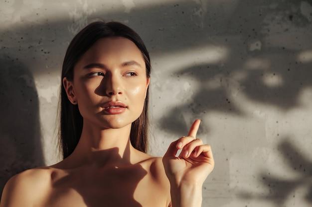Portrait de jeune femme joyeuse et mignonne montre le doigt et regarde au loin sur un vieux fond de mur à l'ombre de la feuille. concept publicitaire de mode de vie sain et de soins personnels. espace de copie pour site ou spa
