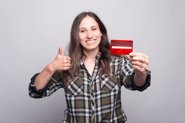 Portrait de jeune femme joyeuse montrant le pouce vers le haut et tenant une carte de crédit rouge. heureux d'acheter en ligne