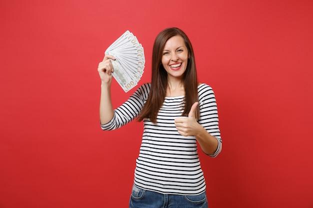 Portrait d'une jeune femme joyeuse montrant le pouce vers le haut et tenant un paquet de dollars, argent comptant isolé sur fond de mur rouge vif. les gens émotions sincères, concept de style de vie. maquette de l'espace de copie.
