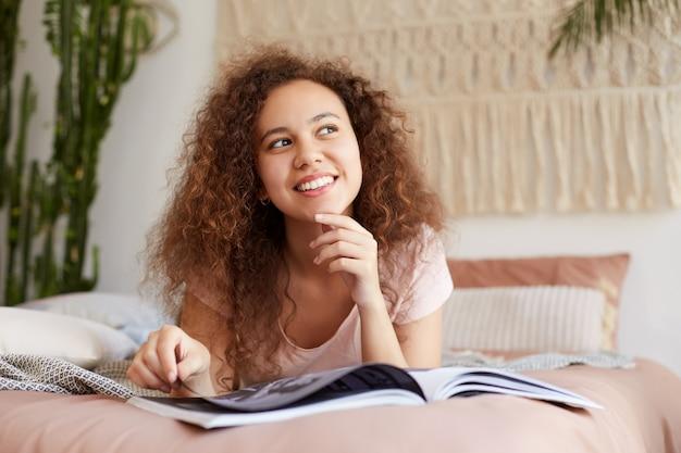 Portrait de jeune femme joyeuse à la peau foncée aux cheveux bouclés, se trouve sur le lit et lit un magazine préféré, profite d'une journée ensoleillée, détourne les yeux et sourit largement.