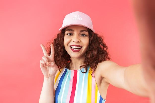Portrait d'une jeune femme joyeuse portant une casquette isolée sur fond rouge