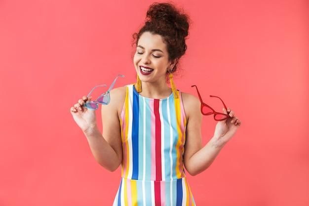 Portrait d'une jeune femme joyeuse portant une robe isolée sur fond rouge, choisissant des lunettes de soleil