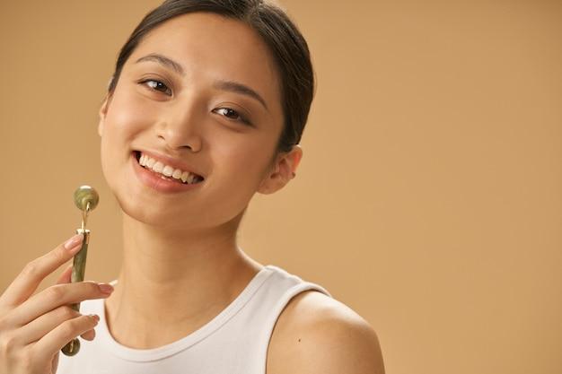 Portrait d'une jeune femme joyeuse souriante à la caméra, utilisant un rouleau de jade pour masser son visage
