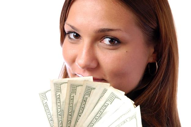 Portrait d'une jeune femme joyeuse tenant des billets d'argent isolés sur fond blanc