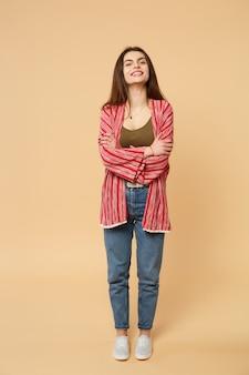 Portrait d'une jeune femme joyeuse en vêtements décontractés à la recherche d'une caméra, tenant les mains croisées isolées sur fond beige pastel en studio. les gens émotions sincères, concept de style de vie. maquette de l'espace de copie.
