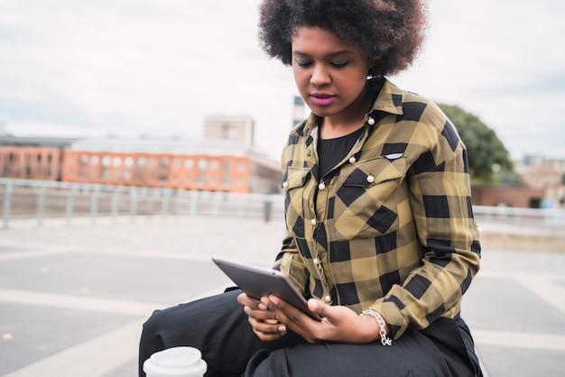 Portrait de jeune femme latine afro-américaine à l'aide de sa tablette numérique alors qu'il était assis sur un banc à l'extérieur. concept technologique.