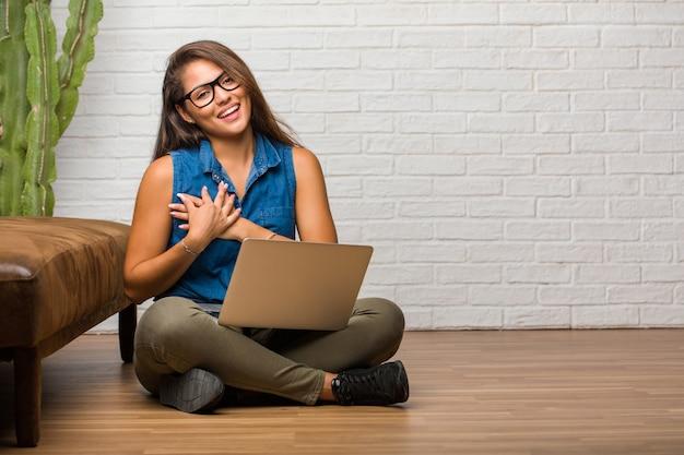 Portrait de jeune femme latine assis sur le sol, faisant un geste romantique