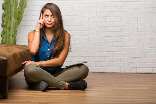 Portrait de jeune femme latine assise sur le sol, pensant et levant les yeux, confuse à propos d'une idée, elle tenterait de trouver une solution. tenant une tablette.
