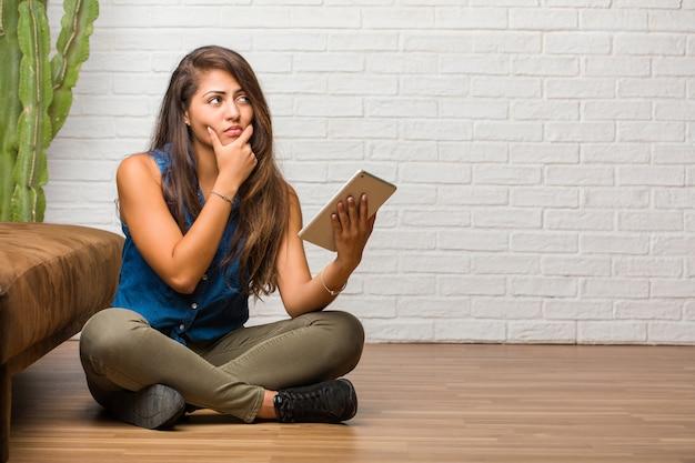 Portrait de jeune femme latine assise sur le sol, pensant et levant les yeux, confuse