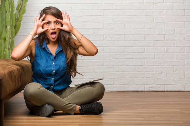 Portrait de jeune femme latine assise sur le sol surprise et choquée, regardant avec des yeux écarquillés, excitée par une offre ou par un nouvel emploi, concept gagnant. tenant une tablette.