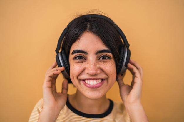 Portrait de jeune femme latine écoutant de la musique avec des écouteurs contre le jaune.
