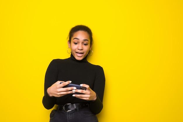 Portrait d'une jeune femme latine joyeuse, jouer à des jeux sur téléphone mobile