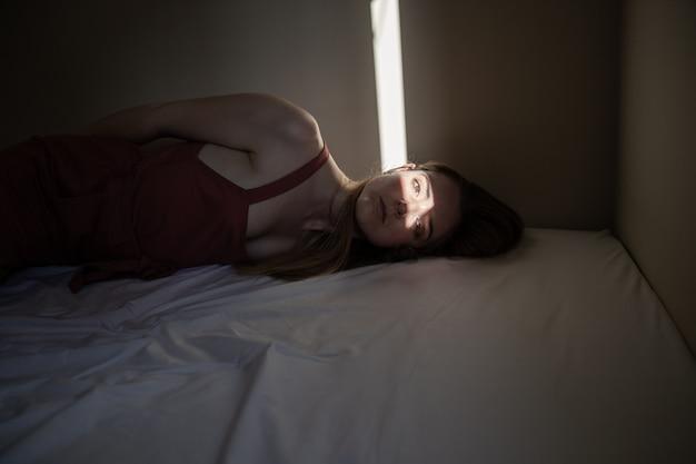 Portrait, de, jeune femme, à, a, ligne lumière, éclairer, elle, yeux, coucher lit