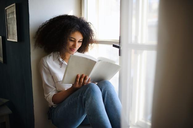 Un portrait de jeune femme avec un livre à l'intérieur à la maison, en train de lire.