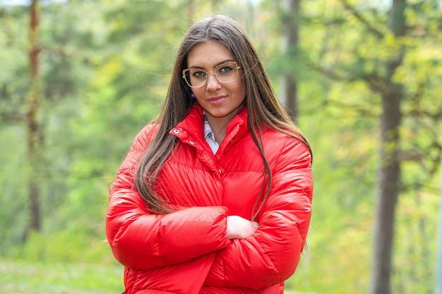 Portrait d'une jeune femme à lunettes, forêt défocalisée
