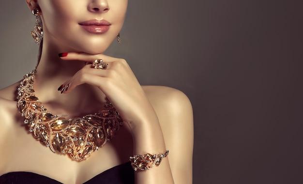 Portrait de jeune femme magnifique vêtue d'un ensemble de bijoux de collier, bague, bracelet et boucles d'oreilles. le mannequin aux yeux bleus montre un maquillage et une manucure attrayants.