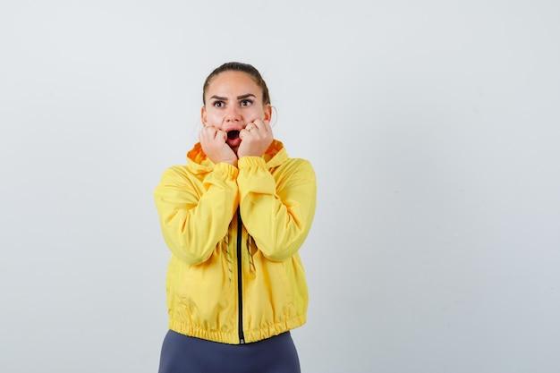 Portrait de jeune femme avec les mains près de la bouche en veste jaune et à la vue de face horrifiée