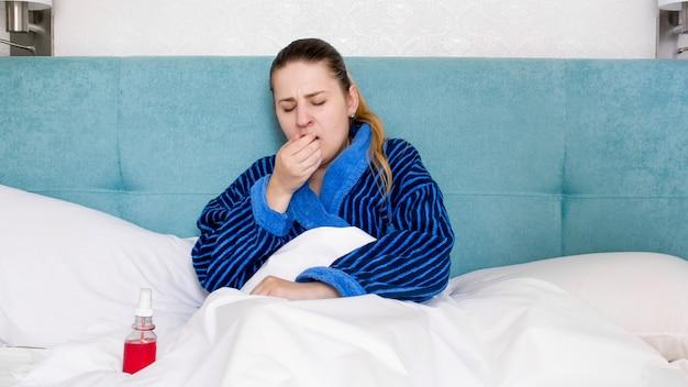 Portrait de jeune femme malade allongée dans son lit et toussant