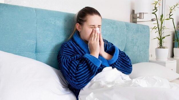 Portrait de jeune femme malade éternuant et se mouchant en position couchée dans son lit