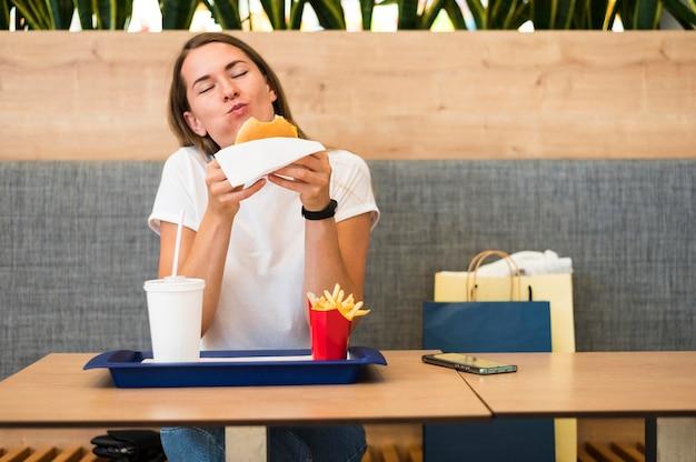 Portrait de jeune femme mangeant de la restauration rapide