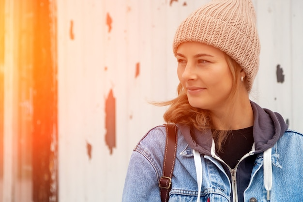 Portrait jeune femme en manteau de jeans bleu, bonnet à tricoter, jeans dans le contexte de l'ancien phare. concept de vacances d'automne au village et style de vie