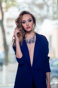 Portrait d'une jeune femme avec maquillage et coiffure, vêtue d'un costume bleu, portant un collier en argent