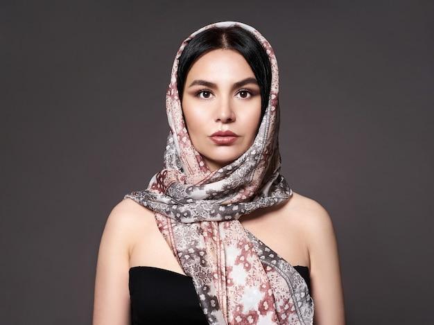 Portrait d'une jeune femme avec un maquillage lumineux et une écharpe à la mode. fond gris. beauté, mode.