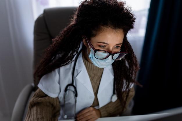 Portrait de jeune femme médecin aux cheveux afro portant des lunettes et un masque de protection utilise son ordinateur personnel.