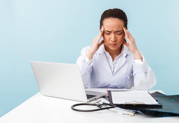 Portrait d'une jeune femme médecin fatigué et ennuyé avec des maux de tête posant isolé sur un mur bleu à l'aide d'un ordinateur portable.