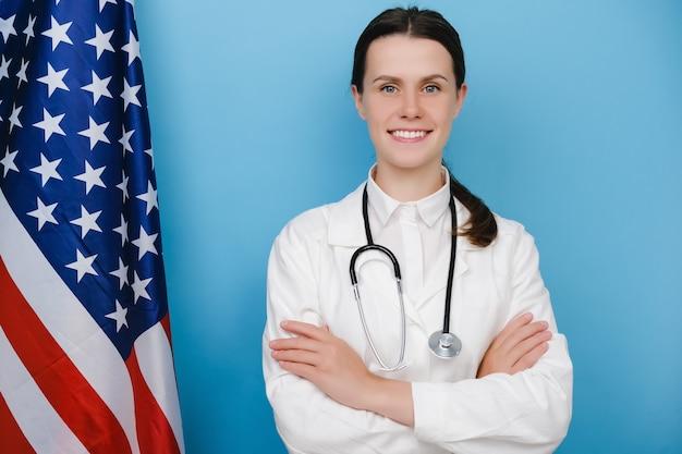 Portrait d'une jeune femme médecin heureuse en uniforme blanc et stéthoscope debout près du drapeau national des états-unis, poitrine croisée, posant sur fond bleu. concept de système de santé national aux états-unis