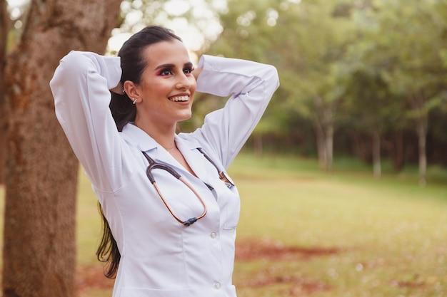 Portrait de jeune femme médecin ou infirmière adulte portant une blouse de laboratoire et un stéthoscope à l'extérieur