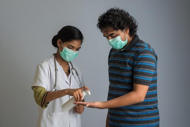 Portrait de jeune femme médecin et jeune homme utilisant ou montrant un gel désinfectant provenant d'une bouteille pour le nettoyage des mains.