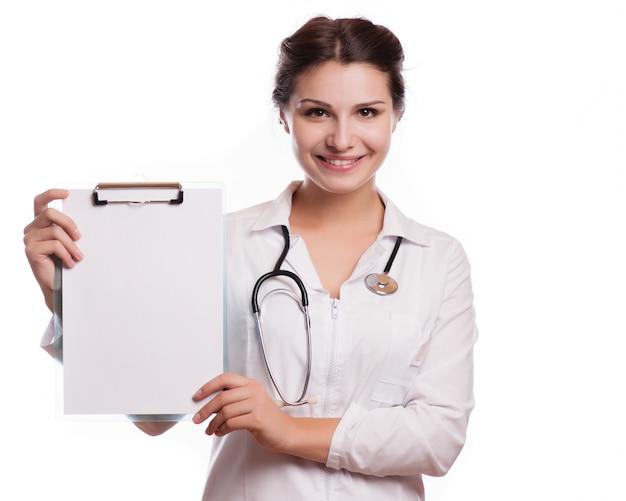 Portrait de jeune femme médecin montrant quelque chose ou copyspase pour le produit ou le texte du signe