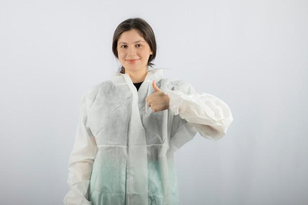 Portrait de jeune femme médecin scientifique en blouse défensive montrant un pouce vers le haut.