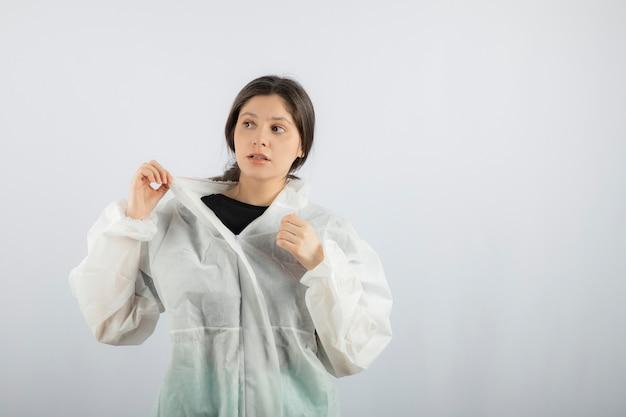 Portrait de jeune femme médecin scientifique en blouse de laboratoire défensive à l'écart.