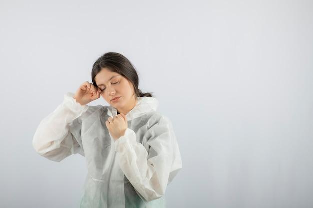 Portrait de jeune femme médecin scientifique en blouse de laboratoire défensive posant.