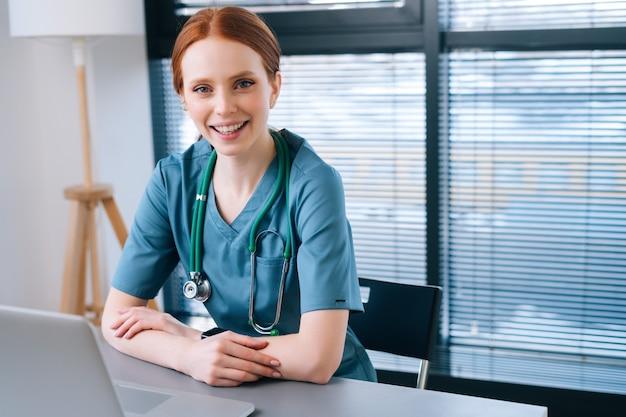 Portrait d'une jeune femme médecin souriante séduisante en uniforme médical bleu vert assis au bureau avec un ordinateur portable sur fond de fenêtre