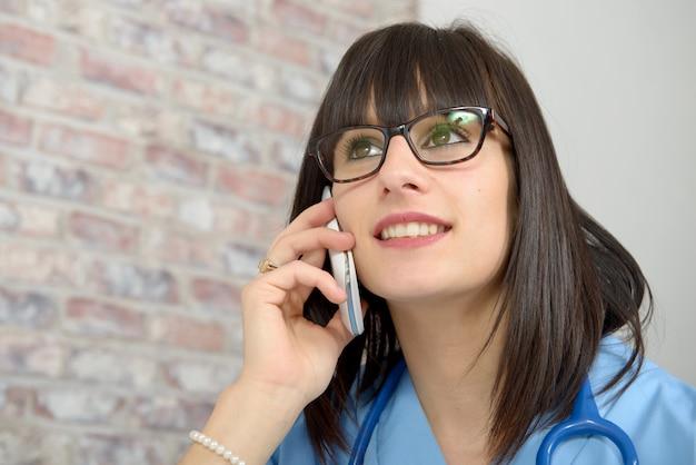 Portrait de jeune femme médicale à l'aide de téléphone
