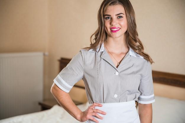 Portrait d'une jeune femme de ménage souriante avec sa main sur la taille
