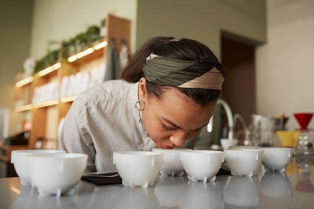Portrait de jeune femme métisse sentant le café lors de l'évaluation de la qualité et du test de dégustation au café, espace de copie
