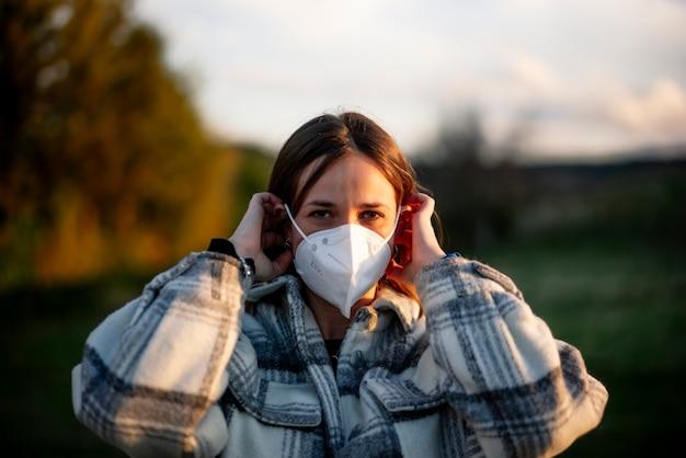 Portrait de jeune femme mettant un masque de protection à l'extérieur