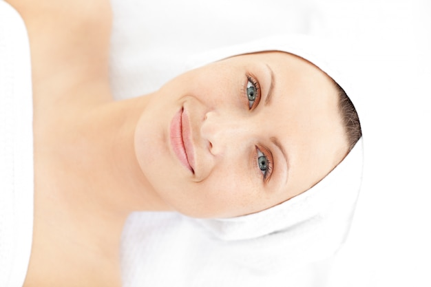 Portrait d'une jeune femme mignonne allongée sur un massage souriant à la caméra