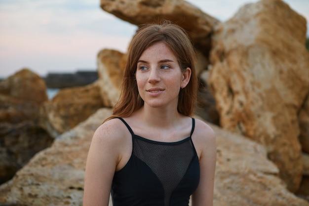 Portrait de jeune femme mignonne au gingembre souriant avec des taches de rousseur est assis sur la plage, regarde rêveusement ailleurs, a l'air positif et heureux.