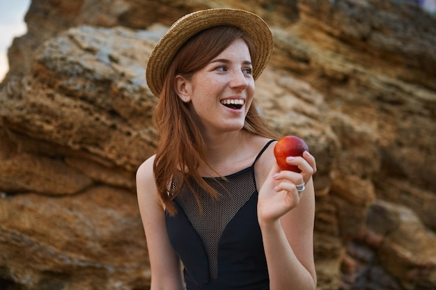 Portrait de jeune femme mignonne de taches de rousseur au gingembre sur la plage, porte un chapeau, mange une pêche, sourit largement et regarde ailleurs, a l'air positif et heureux.