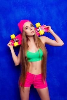 Portrait de jeune femme mince hipster tenant planche à roulettes