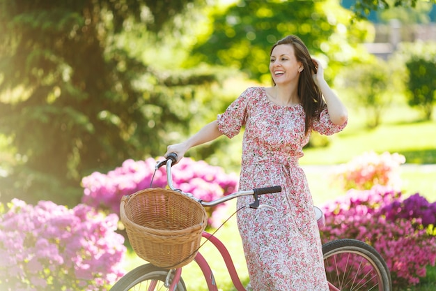 Portrait d'une jeune femme à la mode en longue robe à fleurs rose s'arrêtant pour faire du vélo vintage avec panier pour les achats sur fond de fleurs à l'extérieur. temps de récréation assez féminin au printemps ou au parc d'été
