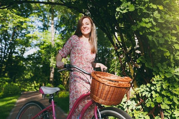 Portrait d'une jeune femme à la mode en longue robe à fleurs rose s'arrêtant pour rouler sous une arche de chêne à vélo avec panier pour les achats, la nourriture ou les fleurs à l'extérieur, jolie récréation féminine au printemps ou dans le parc d'été